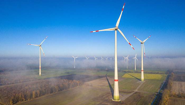 Aerial view of wind turbines in windfarm above mist layer in german countryside in the morning sun. Germany