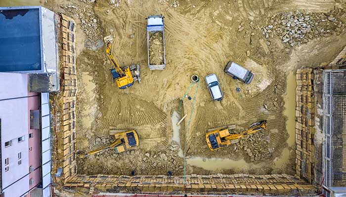 Heavy construction equipment working at the construction site. Aerial view from drone